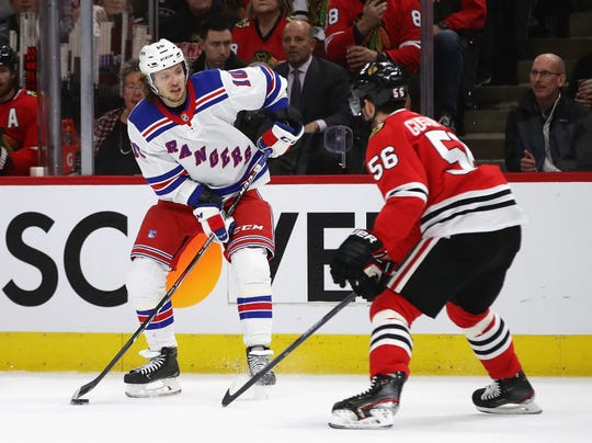 Artemi Panarin #10 of the New York Rangers looks to pass against Erik Gustafsson #56 of the Chicago Blackhawks at the United Center on February 19, 2020 in Chicago, Illinois.