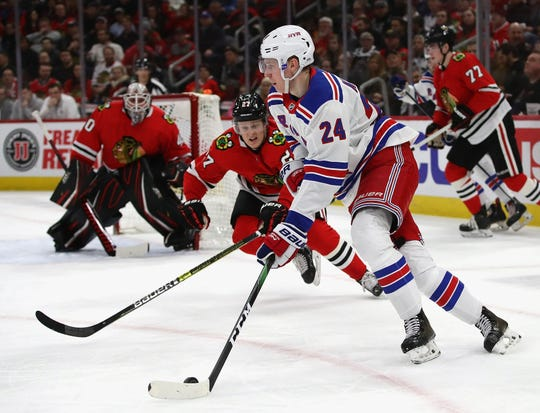 Kaapo Kakko #24 of the New York Rangers looks to pass as Adam Boqvist #27 of the Chicago Blackhawks closes in at the United Center on February 19, 2020 in Chicago, Illinois.