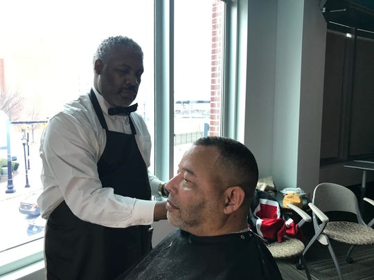 Jerome J. Anderson gives a customer a haircut at the Barclays Black-Owned Small Business Expo.