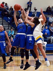 Zanesville's Aayla Mayle, left, Abbi Edwards and Maysville's Kassidy Rock go after a rebound during Maysville's 68-29 win on Tuesday night in a Division II sectional game in Newton Township.