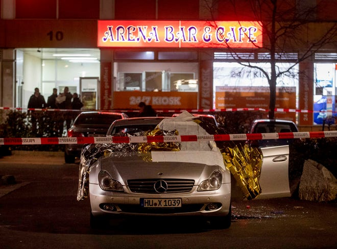 A car with dead bodies stands in front of a bar in Hanua, Germany Thursday, Feb. 20, 2020. German police say several people were shot to death in the city of Hanau on Wednesday evening.