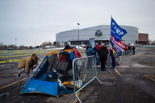 Kristie Long, resident of Fountain, sets up her tent in line to camp overnight, right, outside the Broadmoor World Arena in preparation for President Donald Trump's Colorado Springs campaign rally in Colorado Springs, Colo., on Wednesday, Feb. 19, 2020.