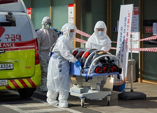 In a Feb. 19, 2020, photo, medial workers wearing protective gears move a patient suspected of contracting the new coronavirus from an ambulance to the Kyungpook National University Hospital in Daegu, South Korea.