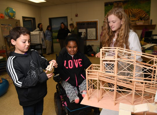 """Campbell Jordan, left, looks at a model of a person in a wheelchair with classmate Wendy Castrejon, left, and teammate Caroline Gray, right, at their model of """"Wheelz Up Zipz"""" during practice for the Starr Elementary Tigerbots robotics team."""