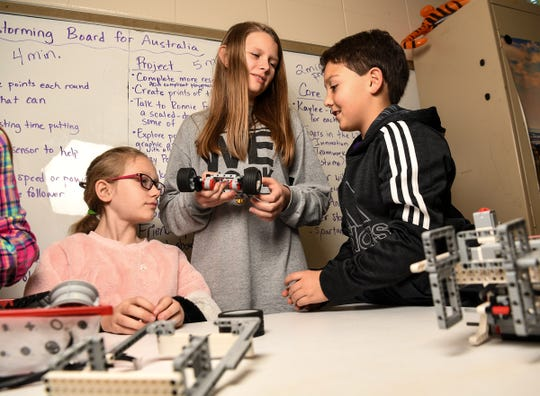 Gracie McGee, left, Kaitlyn Norris, and Campbell Jordan, right, talk about their First Lego League robot during practice for the Starr Elementary Tigerbots robotics team.