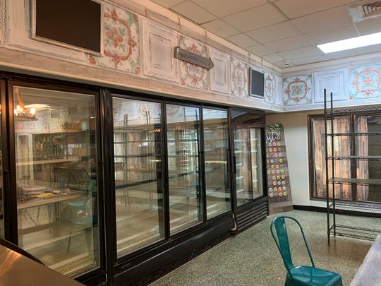 Freezer and refrigerator cases line the walls of Bleu Bear Market in Marlton.