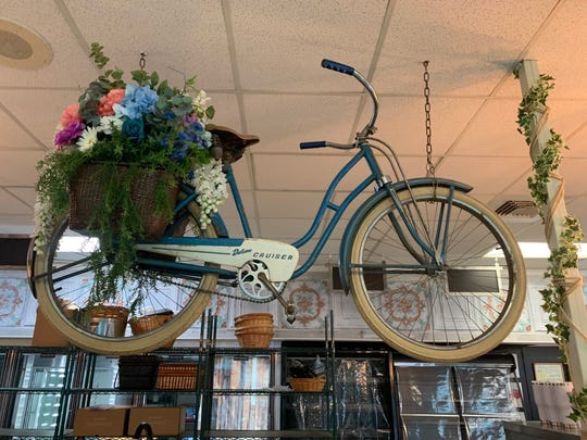A bicycle bedecked with flowers is suspended above the counters of the new Bleu Bear Market in Marlton.