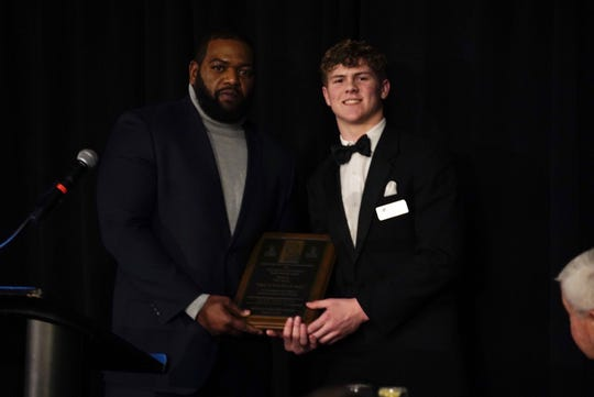 Winton Woods head football coach Andre Parker presents the That's Our Boy award to Alex DeLong of Badin at the That's My Boy Award banquet, Feb. 20, at the Manor House, Mason.