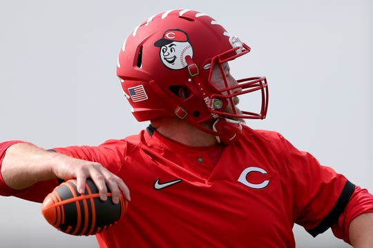 Cincinnati Reds director of strength and conditioning Sean Marohn, who was a former college quarterback, wears a football helmet as he throws footballs during conditioning drills, Friday, Feb. 21, 2020, at the baseball team's spring training facility in Goodyear, Ariz.