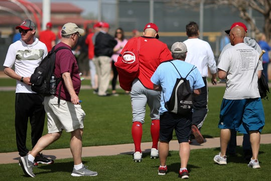 Fans follows Cincinnati Reds center fielder Nick Senzel (15) for autographs as he walks between drills during spring practice, Friday, Feb. 21, 2020, at the baseball team's spring training facility in Goodyear, Ariz.