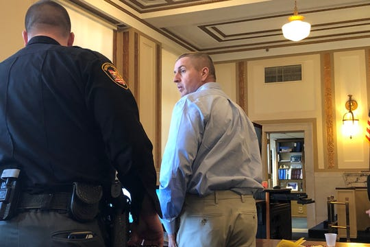 James Rhymer stands so a deputy can lead him out of the courtroom after closing arguments in his trial on Friday, Feb. 21, 2020.