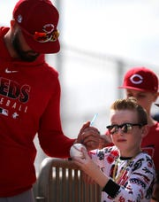 Cincinnati Reds left fielder Jesse Winker (33) signs an autograph for a young fan during spring practice, Friday, Feb. 21, 2020, at the baseball team's spring training facility in Goodyear, Ariz.