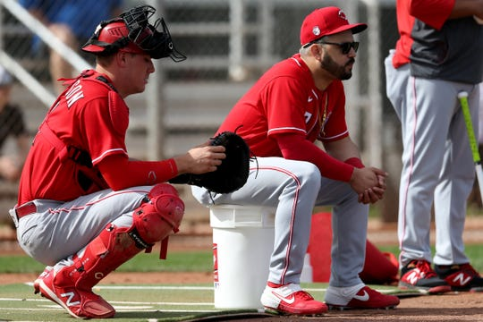 Cincinnati Reds catcher Tyler Stephenson (71) and third baseman Eugenio Suarez (7) await their turns during fielding drills, Friday, Feb. 21, 2020, at the baseball team's spring training facility in Goodyear, Ariz.