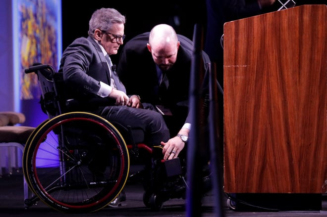 Dan Gilbert gets a hand getting back into his chair as he prepares to leave the stage during the Crain's Newsmakers of the Year event at MGM Grand on Friday, February 21, 2020.