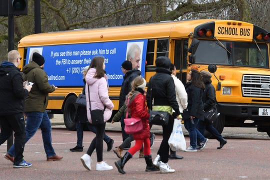 A yellow school bus with a message for the Britain's Prince Andrew, from US lawyer Gloria Allred, drives along The Mall towards Buckingham Palace in London Friday.