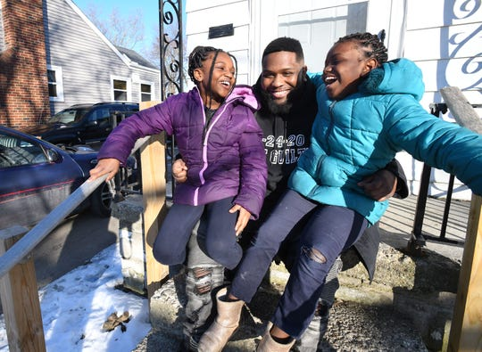 Larry Clemons with his two daughters Jaliyah Clemons, 9, and Jieamah Clemons, 8, smiles on their front porch of their home in Flint.  Clemons has two sons, as well, Jacob Clemons, 11, and Larrion Clemons, 6. Larry Clemons spent 4.5 years in jail while awaiting trial for murder charges before he was ultimately found not guilty.