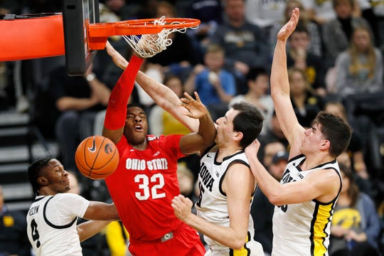 Ohio State forward E.J. Liddell (32) is fouled while driving to the basket between Iowa's Bakari Evelyn, left, Ryan Kriener and Luka Garza, right.