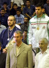 Iranian wrestler Reza Ramazanzadeh, gold medalist, top right, and U.S. wrestler Andy Hrovat, silver medallist, top left, pose for photographers with Iranian deputy of sports Ali Kaffashiyan, left, during the Takhti Wrestling Cup in Tehran, Iran on Friday, May 23, 2003.