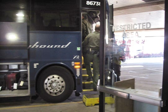 In this Thursday, Feb. 13, 2020 photo, agents for Customs and Border Protection board a Greyhound bus headed for Portland, Ore., at the Spokane Intermodal Center, a terminal for buses and Amtrak, in Spokane, Wash.