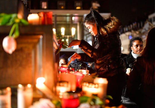 A woman lights a candle at a monument on the market place during a mourning for the victims of the shooting in Hanau, Germany, Thursday, Feb. 20, 2020. A 43-year-old German man shot and killed nine people at several locations in a Frankfurt suburb overnight in attacks that appear to have been motivated by far-right beliefs, officials said Thursday.