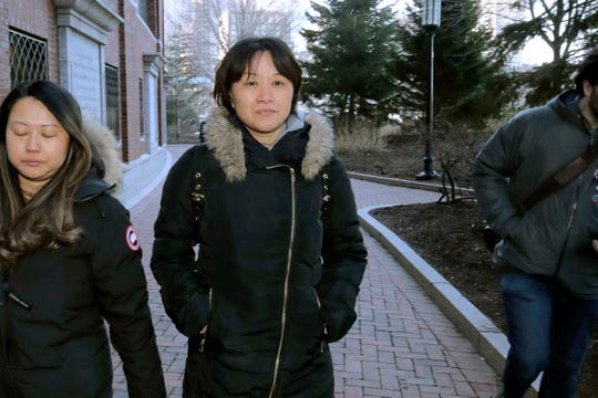 Xiaoning Sui, center, a Chinese national residing in British Columbia, Canada, leaves federal court, Friday, Feb. 21, 2020, in Boston, after pleading guilty to paying $400,000 to get her son into the University of California, Los Angeles, as a fake soccer recruit.
