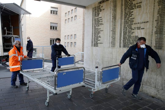 Personnel carry new beds inside the hospital of Codogno, near Lodi in Northern Italy, Friday, Feb. 21,2020. Health officials reported the country's first cases of contagion of COVID-19 in people who had not been in China.