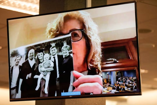 Gillian Millane, mother of murdered British backpacker Grace, holds up a photo during her victim impact statement via video link from England, at the sentencing of the man found guilty of her murder at the Auckland High Court in Auckland, New Zealand, Friday, Feb. 21, 2020.