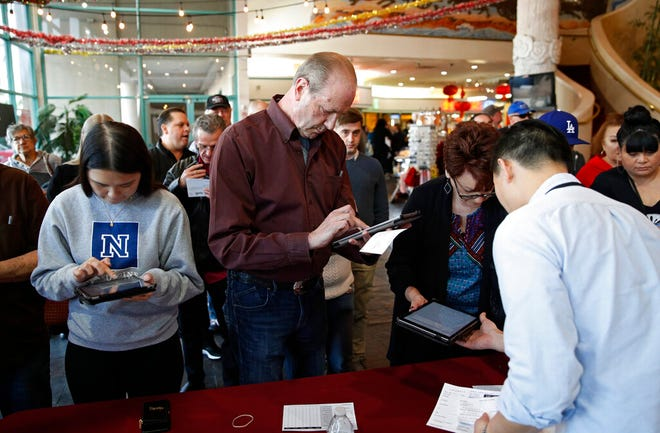 In this Feb. 15, 2020, file photo people sign in on tablets at an early voting location in the Chinatown Plaza, in Las Vegas. Nevada Democrats are hoping to avoid a repeat of the chaos that ensnared the Iowa caucuses, as voters gather across the Silver State on Saturday to make their presidential preferences known.