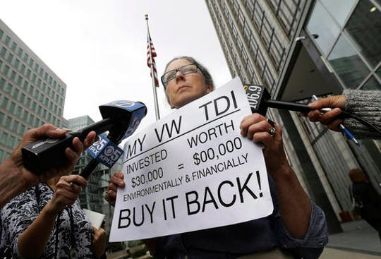 In this April 21, 2016, file photo, Joyce Ertel Hulbert, owner of a 2015 Volkswagen Golf TDI, holds a sign while interviewed outside of the Phillip Burton Federal Building in San Francisco.