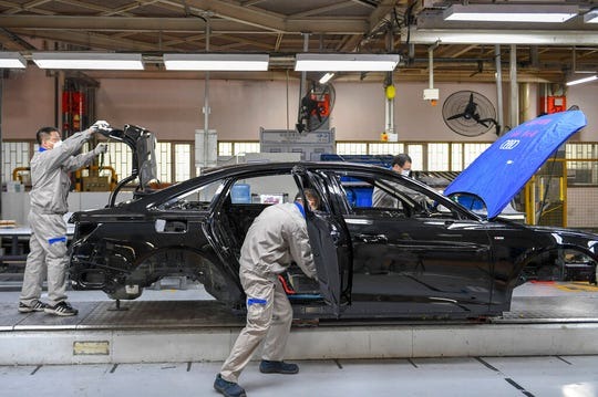 In this Feb. 17, 2020, photo and released by Xinhua News Agency, workers assemble Audi A6 L cars at a workshop of FAW-Volkswagen Automobile Co., Ltd. in Changchun, northeast China's Jilin Province, Automakers are reopening factories in China that were idled by anti-virus controls as they try to reverse a sales slump in their biggest market.