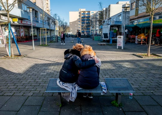 Two woman mourn near a kiosk in Hanau, Germany Friday, two days after a 43-year-old German man shot and killed several people at several locations in a Frankfurt suburb on Wednesday.