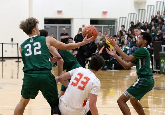 Newfield's Austyn Diaz (32) and teammate Jalen Hardison go for teh ball with Marathon's Kenyon Depuy in between them during the Trojans' 57-54 win in the IAC Small School boys basketball championship game Feb. 20, 2020 at Tompkins Cortland Community College.