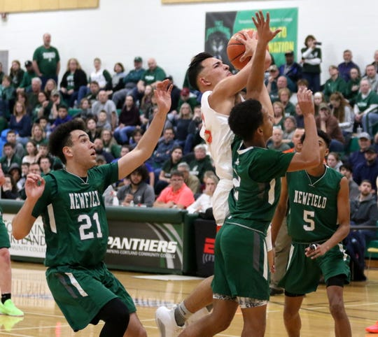 Diego Castellot of Marathon drives the lane as Newfield's LaRon Boykin (21), Jalen Hardison (2) and DaeJahd Leckey (5) defend during the Trojans' 57-54 win in the IAC Small School boys basketball championship game Feb. 20, 2020 at Tompkins Cortland Community College.