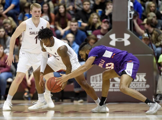 Southern Illinois guard Lance Jones (5)  steals the ball from Evansville guard K.J. Riley (33) during the first half at the Banterra Center on Thursday in Carbondale.