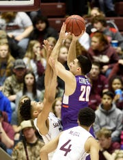 Evansville guard Sam Cunliffe (20) is pressured by Southern Illinois guard Ronnie Suggs (3) as he shoots during the first half at the Banterra Center on Thursday in Carbondale.