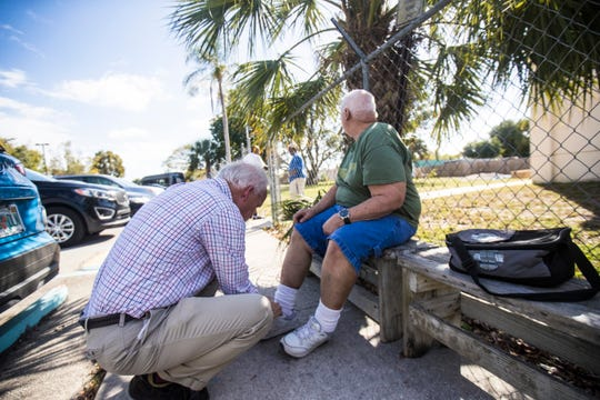 Kevin Lewis, the executive director of LARC helps a LARC client, right, with his shoes on Thursday.  Dozens of clients were affected by the suspension of service by Good Wheels.
