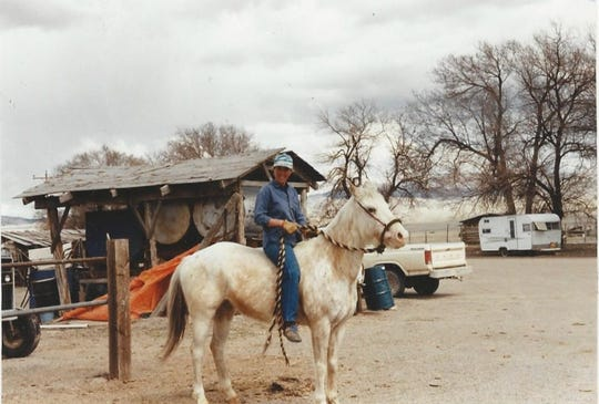 Lisa Schmidt sits on the horse she bought at the auction on the day she brought the mare home. The previous owner thought the horse had never been ridden.