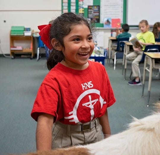 """Kenzi Luna pets a miniature horse that was visiting her school. This academic year, the """"Reading with Rocky"""" programs is serving 250 students in five Henderson schools: AB Chandler, East Heights, Holy Name, Jefferson, and Niagara."""
