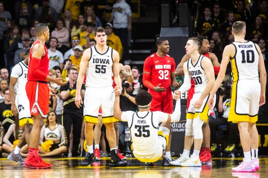 True to its tight-knit form, Iowa players Luka Garza and Joe Wieskamp help up teammate Cordell Pemsl during the Hawkeyes' 85-76 win against Ohio State that wasn't really that close.
