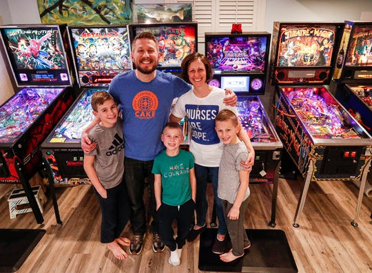The Ross family and their pinball machines in the basement of their home in McCordsville.
