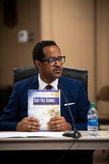 "Superintendent candidate Roderick Richmond presents a book, ""Fight-Free Schools,"" to the school board at the Jackson-Madison County Board of Education during interviews for the superintendent position Feb. 20, 2020."
