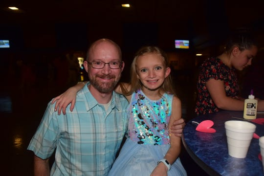 David Wilson with his daughter Katie Wilson, 8, take a break from dancing at the annual Father-Daughter Dance held at Karns High School Saturday, Feb. 15. Katie said she likes to come to the dance with her Dad because she gets to wear a special party dress.