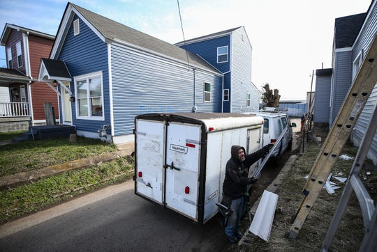 Travis Vozzo of Summers Construction lifts some siding that will go on a house being renovated on Ormsby Avenue in the Shelby Park neighborhood. Several homes in the area have undergone renovation and in some cases, demolition and rebuilding.