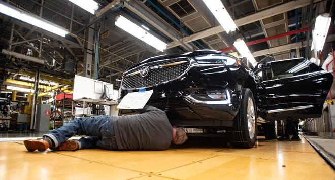 Workers at the GM Lansing Delta Township Assembly plant work on vehicles on Friday, Feb. 21, 2020.