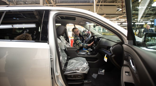 GM general assembly quality department worker Vickie Wils of DeWitt inspects a vehicle as it nears the end of the line at the automaker's Lansing Delta Township Assembly plant on Friday, Feb. 21, 2020.