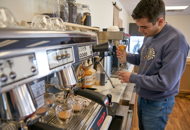 Keaton Sanjur prepares an iced caramel macchiato at his recently opened Keat's Coffee in Ashland.