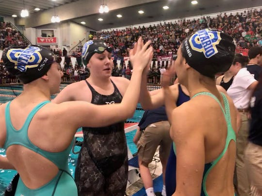 Ava Ruhe gets high-fives from her teammates after Ontario jumps from 23rd seed to 15th and earns All-Ohio honors n the 200 medley relay at the state swim meet