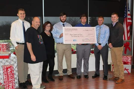 """Becky Kindred-Shelter and her husband receiving the """"Pay It Forward"""" grant from The Ohio State University-Marion students."""