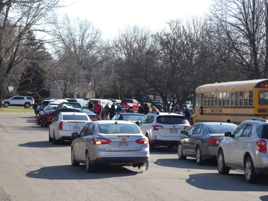 Cars line up outside Benjamin Harrison Elementary School Friday.