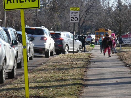 A crossing guard waves kids past the entrance to Benjamin Harrison Elementary School's parking lot Friday afternoon.